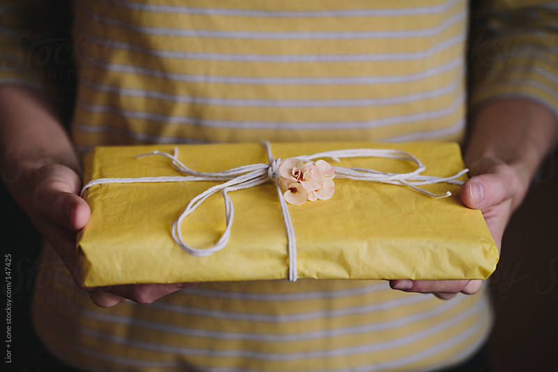 Hands holding a gift wrapped in yellow paper by Lior + Lone for Stocksy United