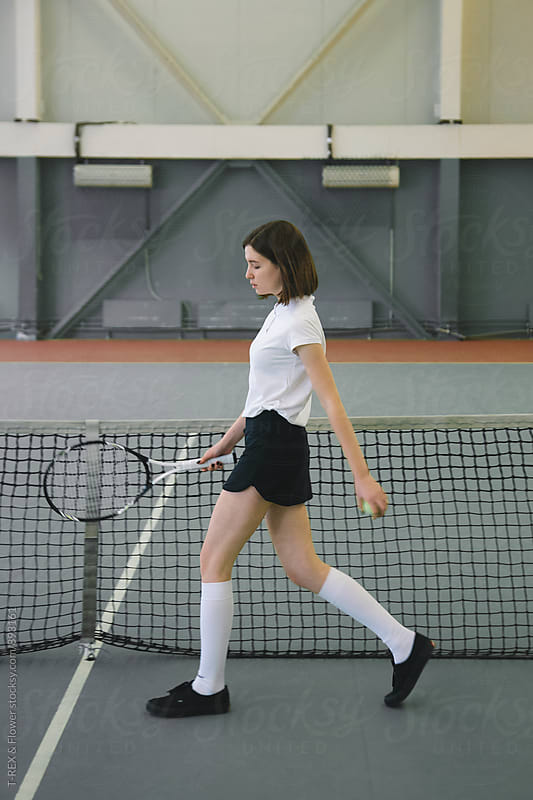 Woman holding racket and ball going along tennis net by T-REX & Flower for Stocksy United