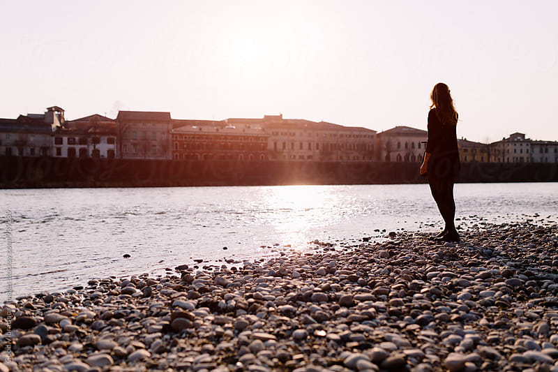Solitary woman by the river at sunset by Good Vibrations Images for Stocksy United