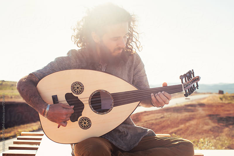 Bearded Young Man Sitting on Roof of White Camper Van and Playing Oud (Mandolin) by Julien L. Balmer for Stocksy United