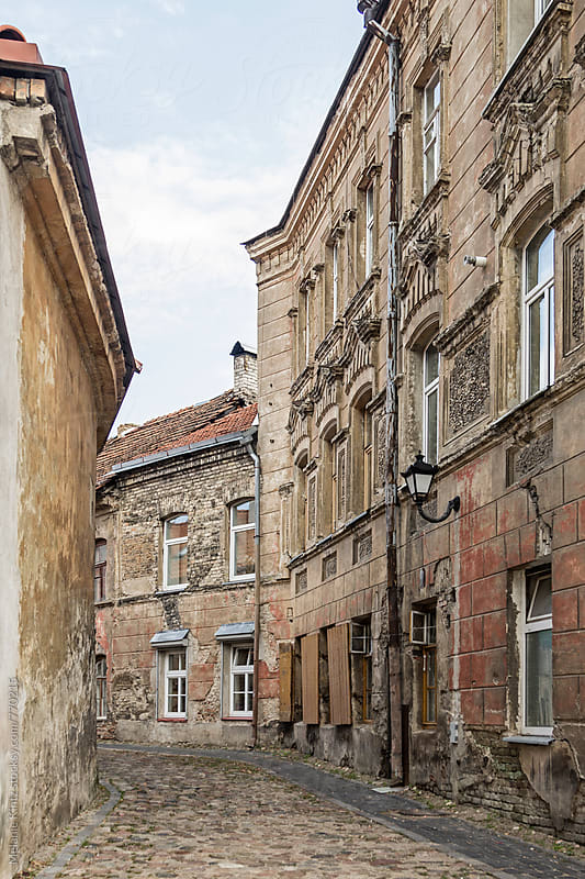 Narrow empty street with old houses in Vilnius by Melanie Kintz for Stocksy United