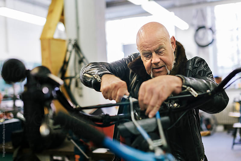 Senior Bicycle Mechanic working on Bike by VegterFoto for Stocksy United