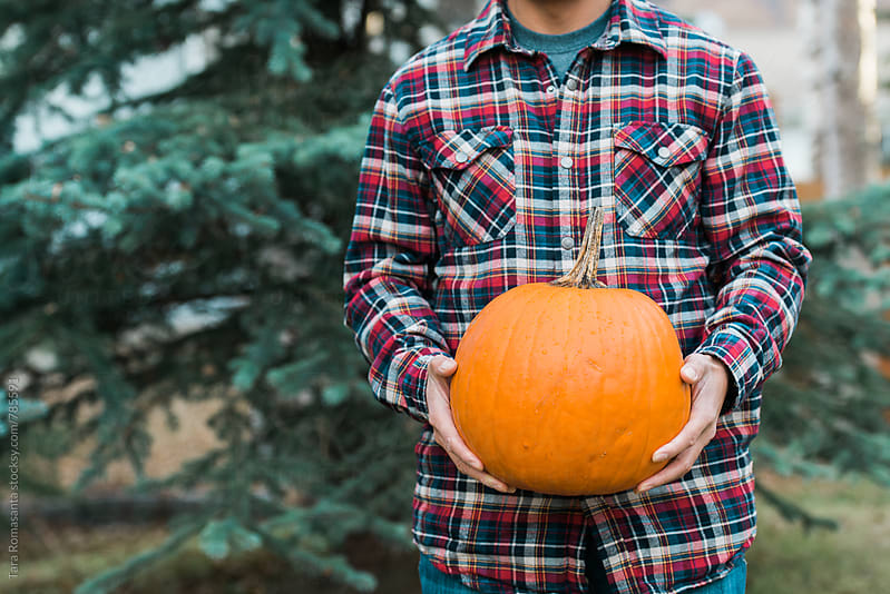 man in plaid shirt holding a pumpkin by Tara Romasanta for Stocksy United