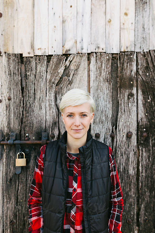 Blonde woman standing in front of a wooden door. by BONNINSTUDIO for Stocksy United