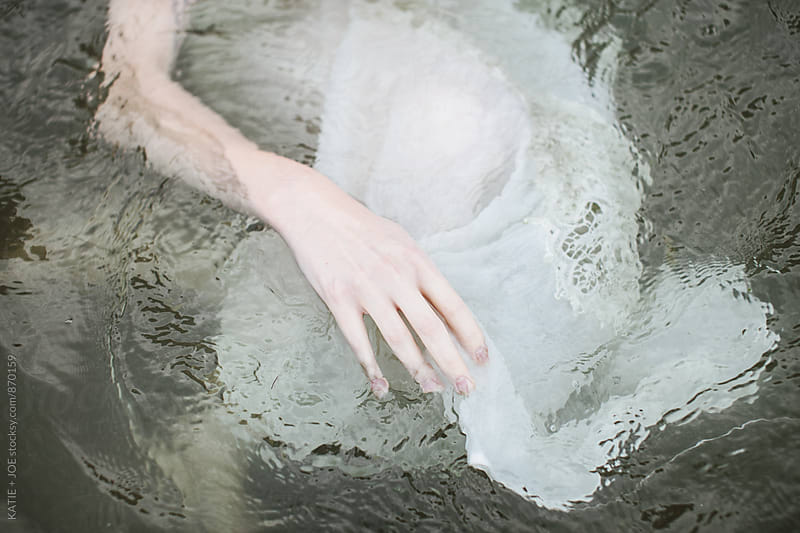 Pale hand of a woman floating in murky water wearing a white dress by KATIE + JOE for Stocksy United