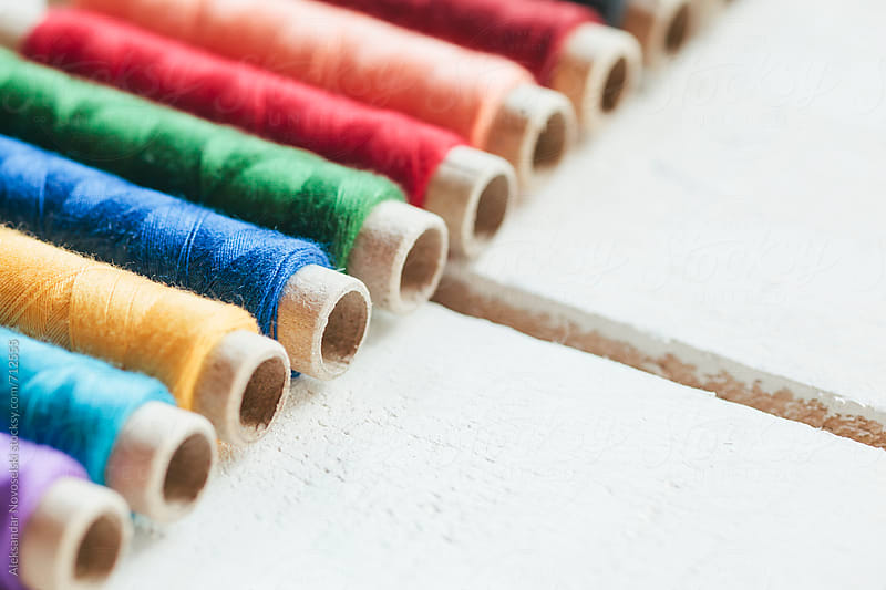 Detail shot of colorful threads on white wooden background by Aleksandar Novoselski for Stocksy United