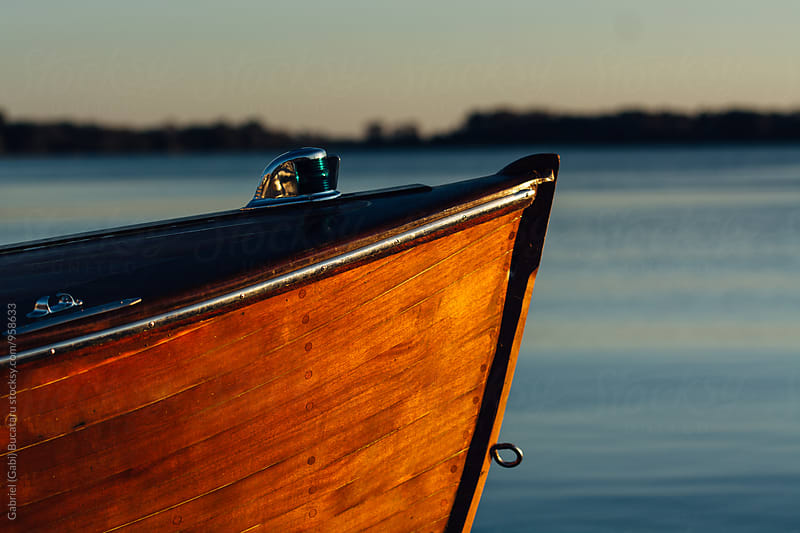 Wooden boat against a blue lake by Gabriel (Gabi) Bucataru for Stocksy United