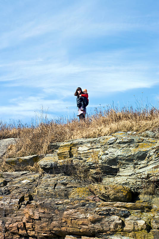 Son rides on his mother's back standing on top of a large rock by Cara Dolan for Stocksy United