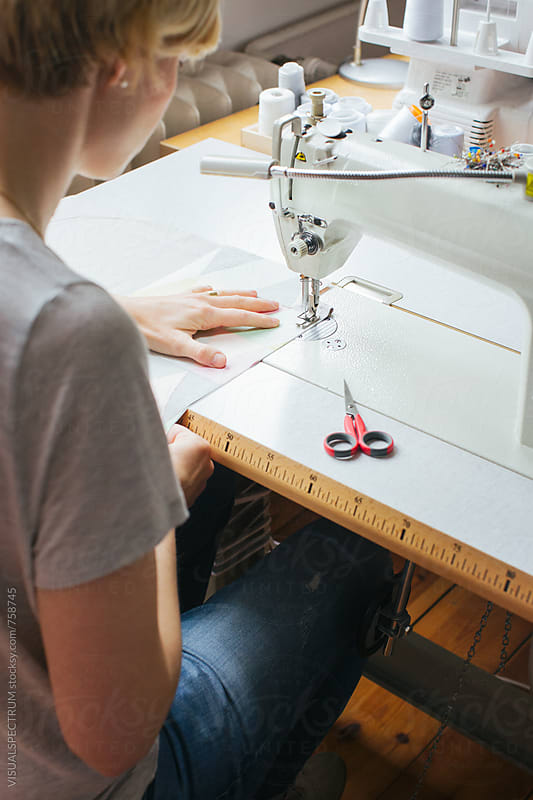 Blond Caucasian Couturier Working on Sewing Machine in Bright Dressmaking Atelier by Julien L. Balmer for Stocksy United