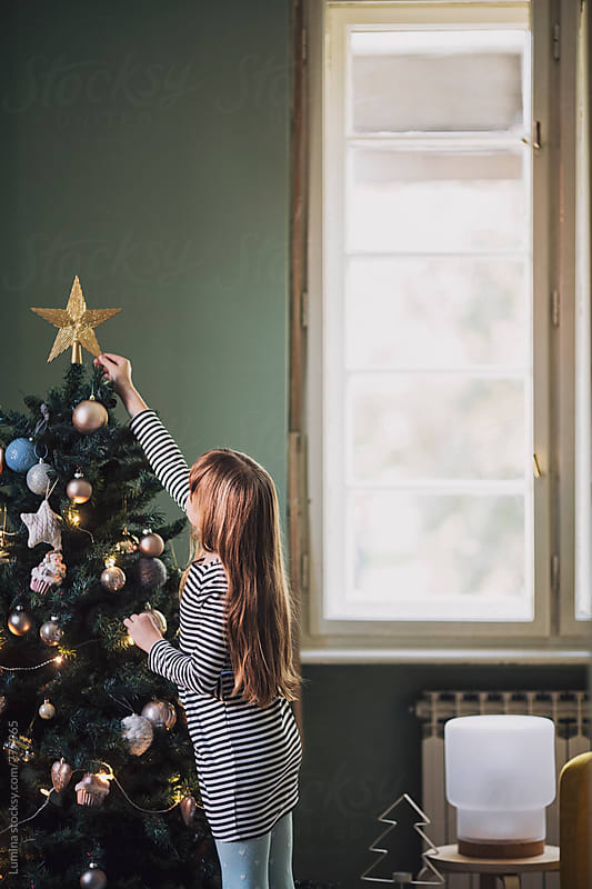 Cute Girl Decorating the Christmas Tree by Lumina for Stocksy United
