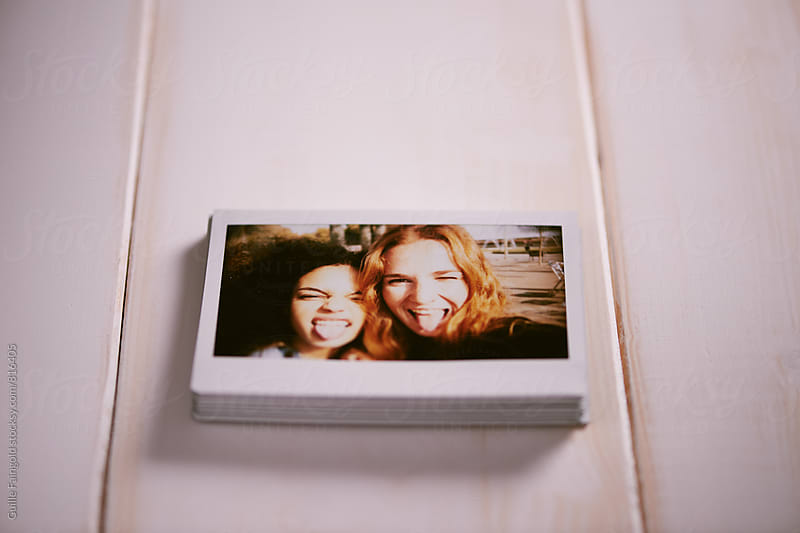 Pile of instant photos of best friends by Guille Faingold for Stocksy United