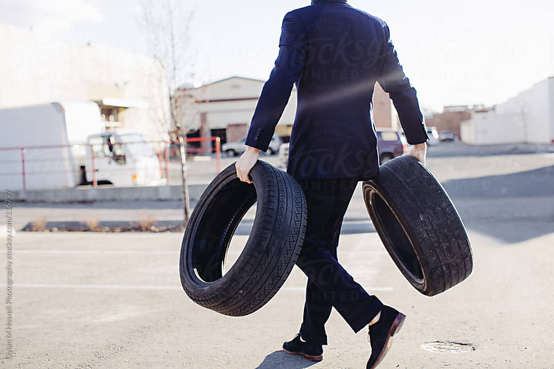 man in suit holding tires by Dylan M Howell Photography for Stocksy United