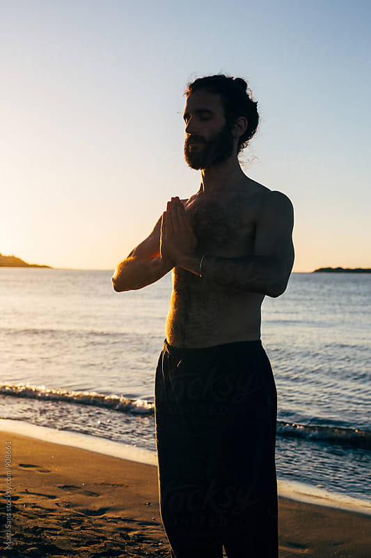 Bearded man meditating on beach by Martí Sans for Stocksy United