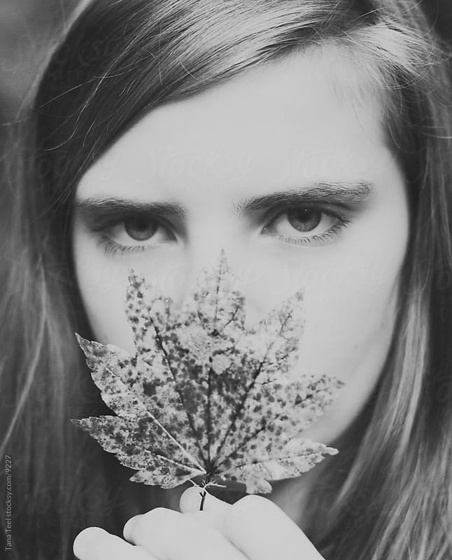 Young girl holding leaf in front of face.  by Tana Teel for Stocksy United