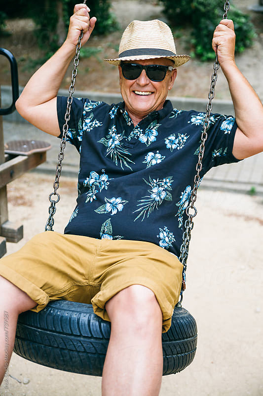 Happy stylish senior man playing on a swing in a children park, wearing sunglasses and a straw hat by Inuk Studio for Stocksy United