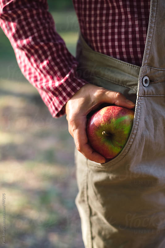 Woman putting just picked apple in her pocket by Pixel Stories for Stocksy United