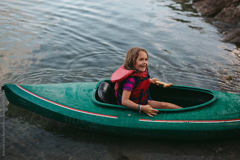 Young caucasian girl enjoying kayak on lake in summer by Rob and Julia Campbell for Stocksy United