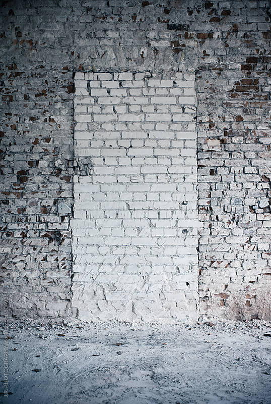 Door in a brick wall that has been bricked up by J.R. PHOTOGRAPHY for Stocksy United