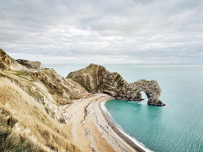 A natural rock arch on the coast of the UK by James Ross for Stocksy United