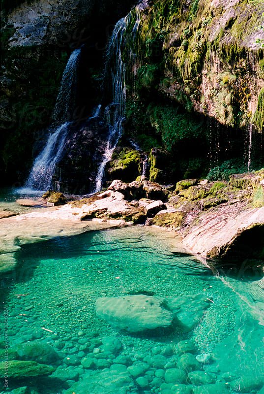 Waterfall and  turquoise lake by Bor Cvetko for Stocksy United