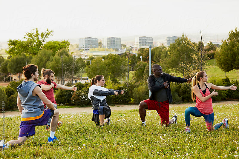 Multiethnic Athletes Doing Stretching Exercise On Grass by ALTO IMAGES for Stocksy United