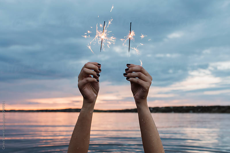 Person underwater holding sparklers  by Carey Shaw for Stocksy United