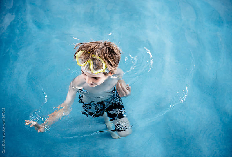 Boy splashes in a pool while wearing a diving mask on his head by Cara Dolan for Stocksy United