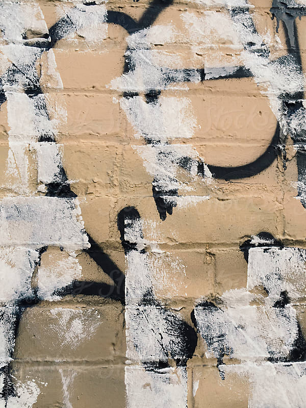 Graffiti markings and paint on building wall, close up by Paul Edmondson for Stocksy United