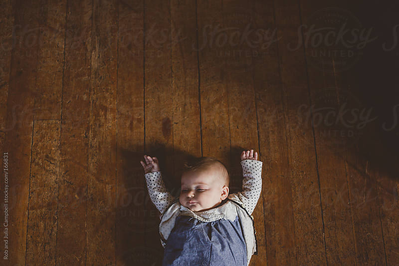 Cute sleeping baby girl on old wood floor by Rob and Julia Campbell for Stocksy United