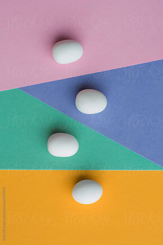 White egg shaped candies on  a colorful background by Irina Efremova for Stocksy United