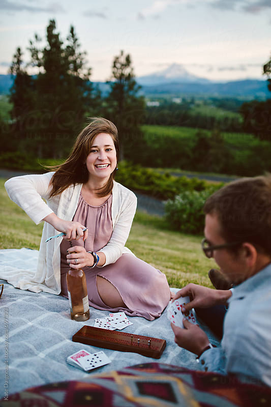 Cute couple having a sunset picnic by Kate Daigneault for Stocksy United