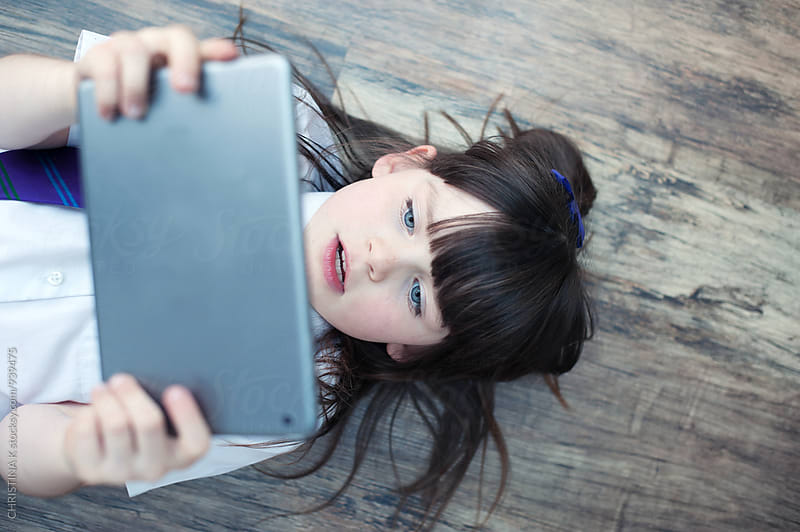 Schoolgirl watching a digital tablet by CHRISTINA K for Stocksy United