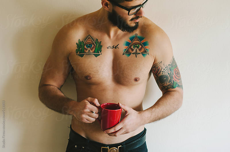 Tattooed shirtless man drinking coffee. by Studio Firma for Stocksy United