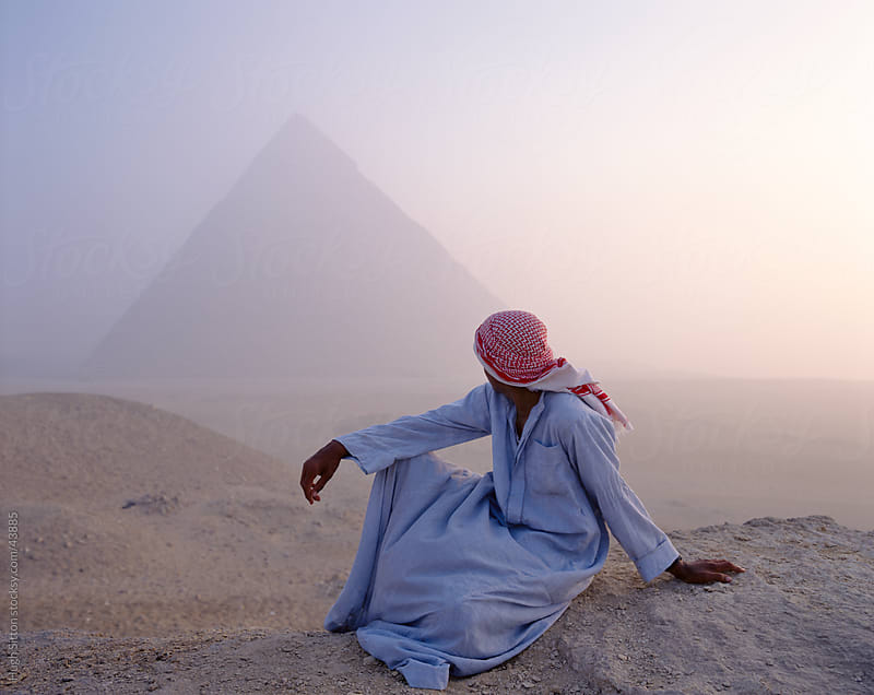Arab sitting infront on the the Giza Pyramids in the early morning. by Hugh Sitton for Stocksy United