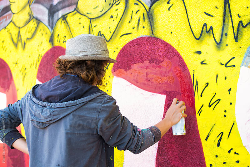 Female graffiti artist writing on wall by Pixel Stories for Stocksy United