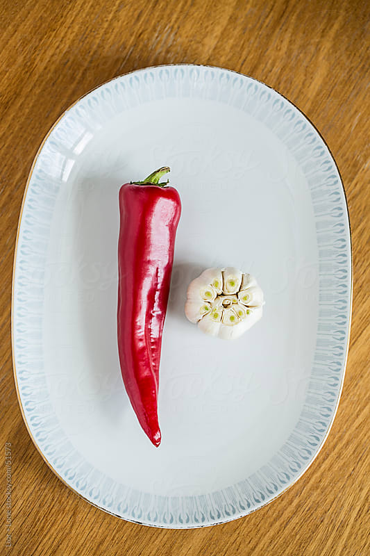 fresh red pepper and garlic bulb on vintage plate by Lior + Lone for Stocksy United