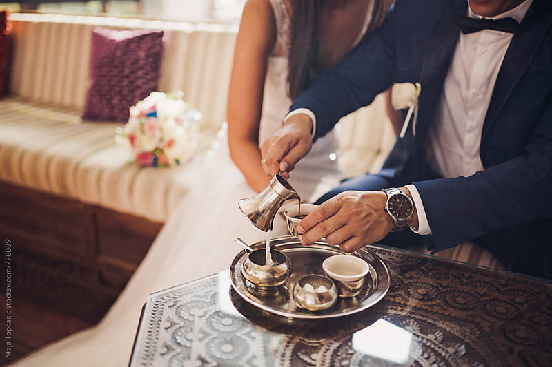 Bride and groom laughing and drinking coffee in an oriental coffee shop by Maja Topcagic for Stocksy United
