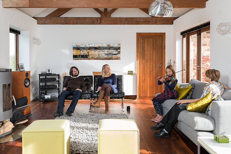 Family in a contemporary living room with daughter playing the violin. by Paul Phillips for Stocksy United