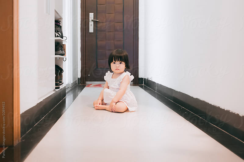 Asian baby girl sitting at home by Pansfun Images for Stocksy United