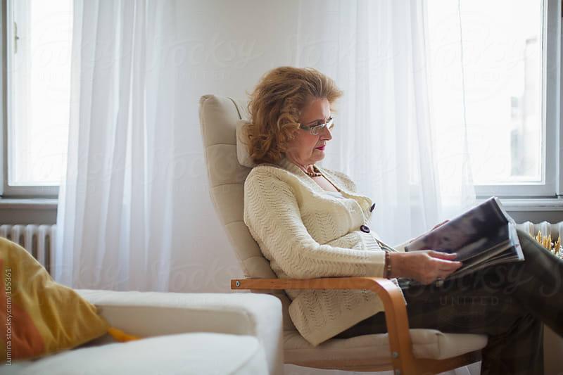 Senior Woman Reading a Magazine by Lumina for Stocksy United
