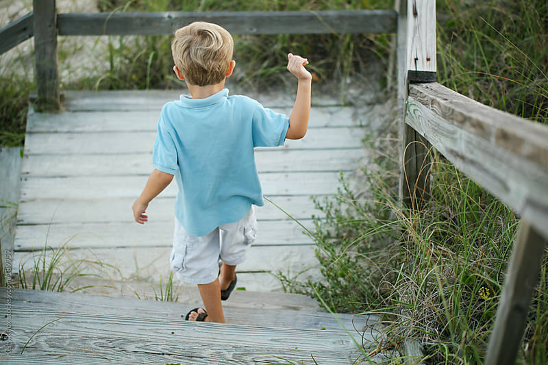 young boy walking down steps to the beach by Kelly Knox for Stocksy United