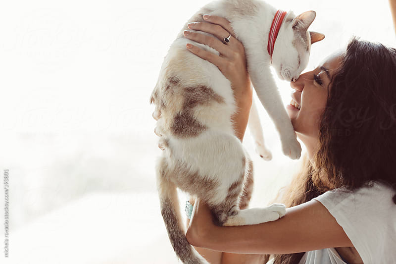 Young woman having fun with her cat by michela ravasio for Stocksy United