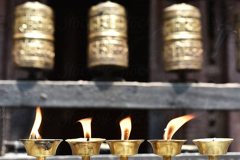 Pray wheels and candles in a temple of Nepal by Bisual Studio for Stocksy United