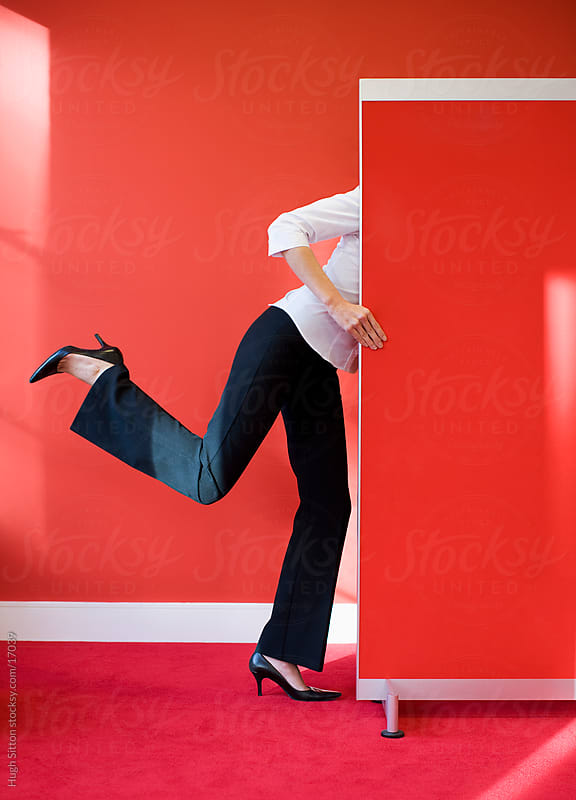 Businesswoman balancing on one foot behind screen. by Hugh Sitton for Stocksy United