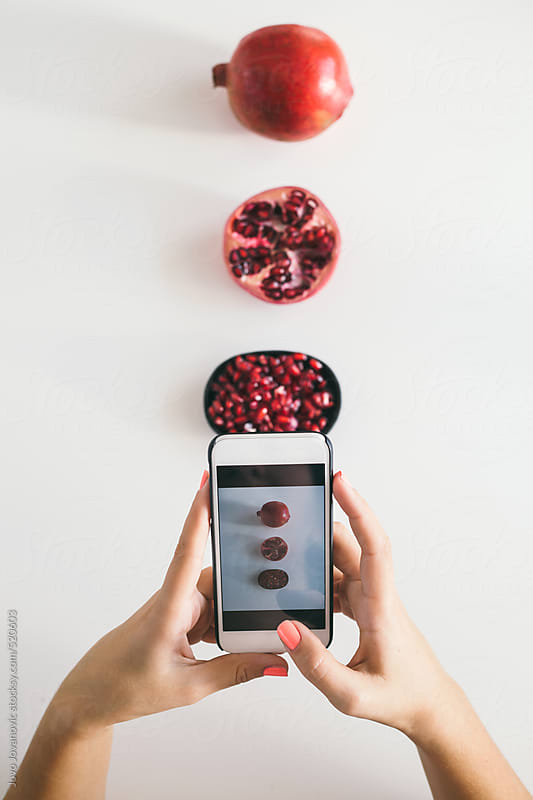 Woman taking a photo of pomegranate on white table by Jovo Jovanovic for Stocksy United