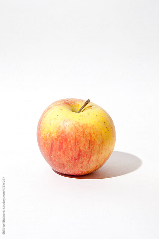 A single apple isolated against a white background. by Shikhar Bhattarai for Stocksy United