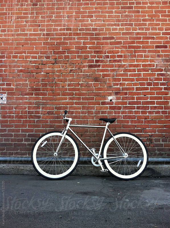 Fixed gear bicycle against red brick wall by Kurt Heim for Stocksy United