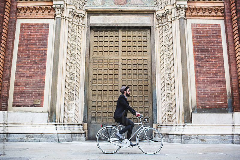 Young man riding a bicycle in front of an ancient neo-Gothic Church by michela ravasio for Stocksy United