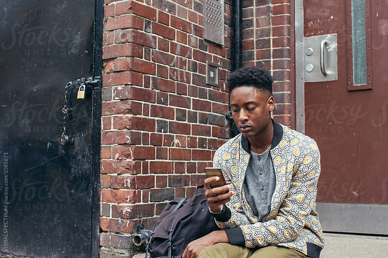 Young Black Man Sitting in Front of Typical London Home and Using Smartphone by Julien L. Balmer for Stocksy United