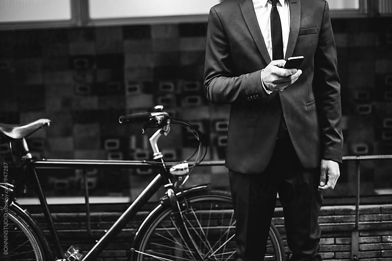 Closeup of a businessman using his phone next to bicycle on the street. by BONNINSTUDIO for Stocksy United